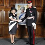 Mrs Janet Chisholm and the Lord Lieutenant with a portrait of the Queen